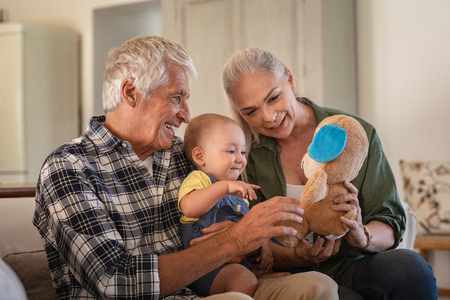 Toddler playing with old grandparents and teddy bear stuff toy. Cheerful grandfather and smiling grandmother showing soft toy to grandchild. Cute toddler boy playing with senior man and woman sitting on couch.