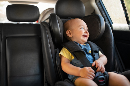 Portrait of cute smiling toddler sitting in car seat and looking outside the window. Little boy sitting in safety chair and laughing alone with copy spce. Happy child having fun in safety car seat while enjoy the travel. Stock Photo