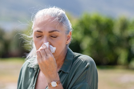 Senior woman with tissue having flu or allergy at park. Mature sick woman with grey hair suffering from cold outdoor. Old ill lady with closed eyes blowing nose with copy space.