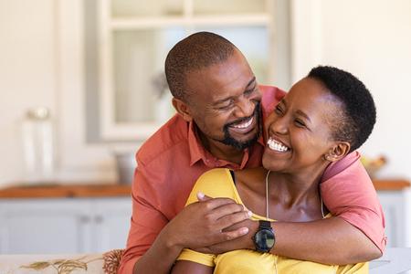 Ouder zwart paar omarmen op de bank terwijl ze naar elkaar kijken. Romantische zwarte man die vrouw van achteren omhelst terwijl hij samen lacht. Gelukkige Afrikaanse vrouw en man die in perfecte harmonie liefhebben. Stockfoto