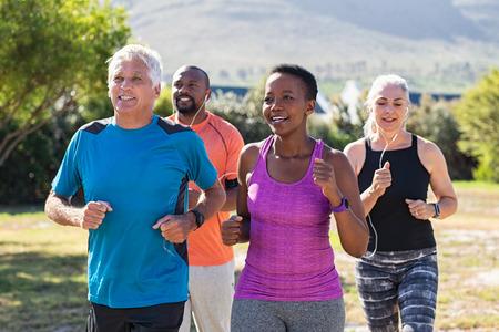 Gesunde Gruppe reifer Menschen, die im Park auf der Strecke joggen. Glückliches älteres Paar, das mit afrikanischen Freunden im Park läuft. Multiethnische Freunde mittleren Alters, die zusammen im Freien trainieren.