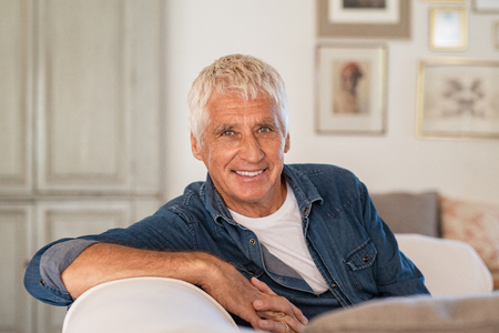 Happy senior man sitting on comfortable sofa in living room. Old man with grey hair relaxing on couch and smiling while looking at camera. Elderly man enjoying retirement at home.
