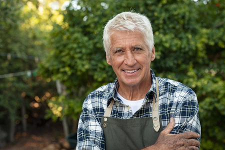 Portrait of happy senior farmer smiling and looking at camera. Cheerful old man with grey hair wearing apron outdoor with copy space. Satisfied smiling gardener in field standing with folded arms.