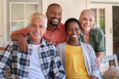 Senior couple with mature man and african woman posing for a photo sitting at courtyard. Portrait of happy multiethnic people sitting on couch under patio. Cheerful men and beautiful women looking at camera.