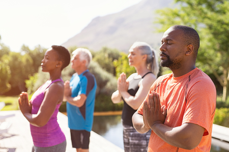 Vier ältere Menschen, die mit verbundenen Händen und geschlossenen Augen meditieren, atmen tief ein. Multiethnische Gruppe, die während der Yoga-Sitzung im Freien Atemübungen macht. Klasse reifer Menschen, die mit verbundenen Händen meditieren und sich gemeinsam im Park entspannen. Standard-Bild