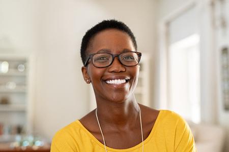 Retrato de mujer joven en casa con gafas. Hermosa mujer madura con anteojos y mirando a cámara. Señora afroamericana alegre con gafas y pelo corto.