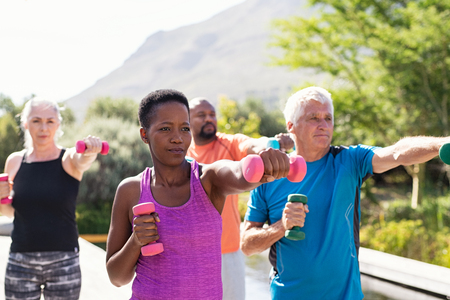 Happy senior and mature couples exercising with dumbbells. Healthy multiethnic people exercising using dumbbells outdoor. African couple and senior friends in sportswear stretching arms holding colorful dumbbells at park. Stock Photo