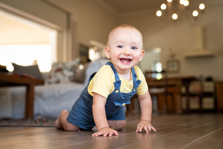 Happy smiling kid crawling on floor at home and looking at camera. Little cute boy taking his first steps while making a funny face. Portrait of toddler crawling on wooden floor at home while laughing.