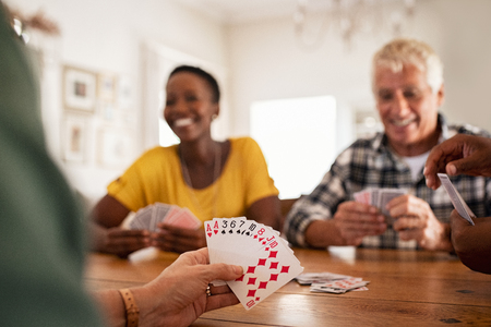 Closeup of woman hand holding playing cards. Group of mature friends relaxing and playing cards together. Senior people and african woman enjoying weekend by playing a game at home while sitting on wooden table.