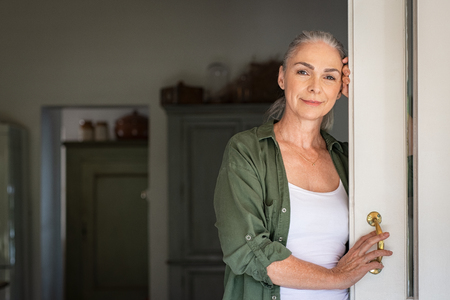 Portrait of senior woman standing while leaning against door at home and looking at camera. Smiling mature woman standing at doorway and looking at camera. Portrait of old lady relaxing and thinking with copy space. Banco de Imagens - 124983070
