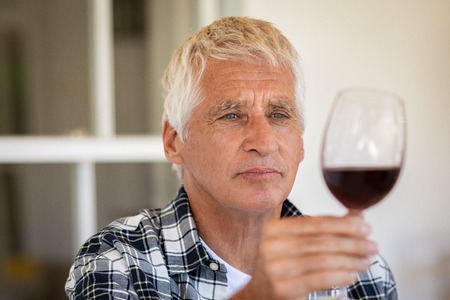 Senior man holding and looking through a glass of red wine. Old man tasting red wine at home. Retired man inspecting quality of wine during wine tasting, quality control.