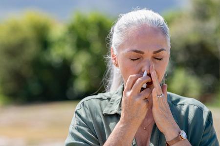 Mujer mayor que tiene gripe con aerosol nasal para ayudarse a sí misma. Mujer que usa un aerosol nasal en el parque para alergias. Mujer madura enferma con canas inhalando medicamentos contra la alergia. Foto de archivo