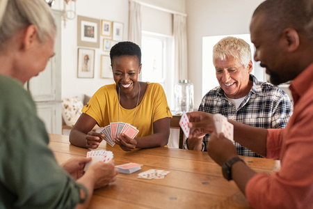 Retired multiethnic people playing cards together at home. Happy senior friends with african couple playing cards. Cheerful active seniors playing game at lunch table. Stock Photo