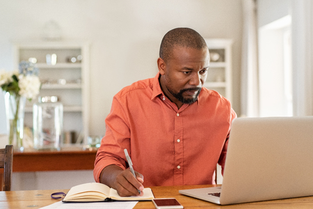 Mature man working on laptop while taking notes. Businessman working at home with computer while writing on agenda. African man managing home finance, reviewing bank account and using laptop in living room. Banque d'images