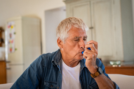 Senior man using asthma inhaler for relief an attack at home. Old man using asthma inhaler for preventing attack. Mature man using medical inhaler to prevent and treat wheezing and shortness of breath caused by allergy.