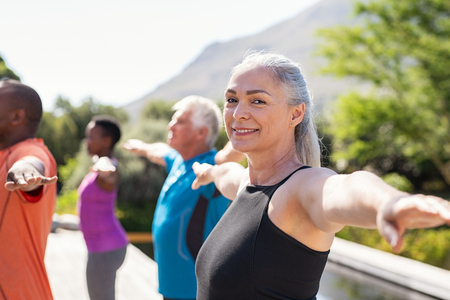 Portrait of happy senior woman practicing yoga outdoor with fitness class. Beautiful mature woman stretching her arms and looking at camera outdoor. Portrait of smiling serene lady with outstretched arms at park. Stock Photo
