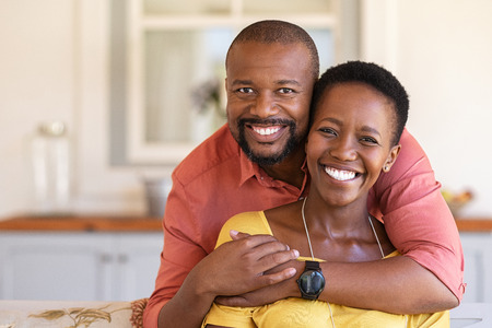 Happy mature black couple bonding to each other and smiling while sitting on couch. Portrait of smiling black man embrace his wife from behind and looking at camera. Smiling husband and beautiful woman laughing. Stock Photo