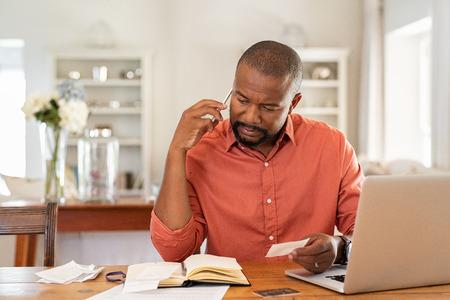 Volwassen man die rekeningen betaalt met laptop terwijl hij telefoneert. Nadenkende man thuis in gesprek via smartphone tijdens het controleren van bonnen. Bezorgde afrikaanse man bespreekt de kosten via de telefoon met een bankverzekering.