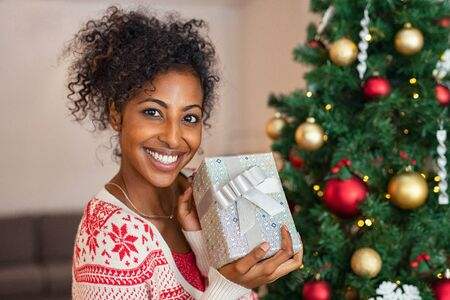 Portrait of smiling african woman wearing christmas sweater and holding silver present box near tree. Young woman showing her gift and looking at camera. Happy pretty girl under new year tree with xmas present.