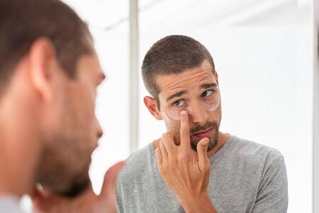 Jonge man die voor zijn rimpels onder de ogen zorgt en anti-aging oogcrème aanbrengt. Man huidverzorging gezichtsbehandeling crème toe te passen op het gezicht in de badkamer. Knappe jongen die vochtinbrengende crème aanbrengt en naar zichzelf kijkt terwijl hij voor de spiegel staat. Stockfoto