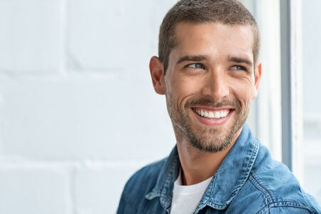 Confident young man looking away with big smile. Happy handsome guy looking through window thinking about the future. Closeup face of smiling casual man imagine with copy space. Stock Photo