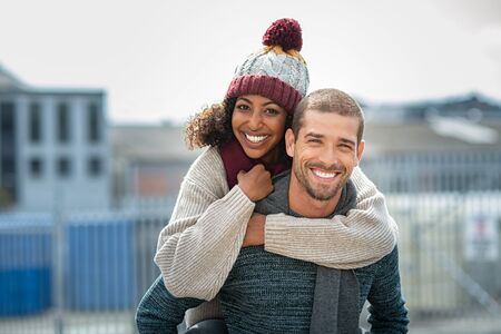 Portrait of young man giving piggyback ride to african woman in the city. Happy boyfriend and smiling girlfriend wearing sweater and wool scarf looking at camera. Multiethnic couple having fun in street during winter season. Imagens