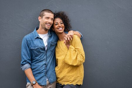 Young multiethnic couple in love isolated on grey background looking up and thinking about their future together. Smiling man and african woman in casual hugging and looking away while planning the future. Cheerful couple holding hands while leaning on wall. Reklamní fotografie