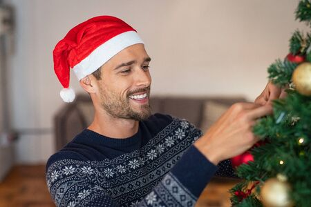 Happy man decorating christmas tree at home with santa claus hat. Handsome guy wearing xmas sweater decorating christmas tree. Man standing and decorating tree with golden baubles during winter holiday. Imagens