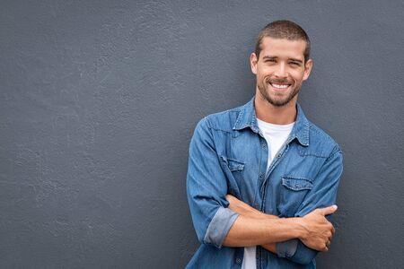 Portret van een knappe jongeman in een casual denim shirt die zijn armen gekruist houdt en glimlacht terwijl hij tegen een grijze achtergrond staat. Stijlvolle en zelfverzekerde man leunend tegen grijze muur met kopieerruimte. Vrolijke vriendelijke man lachen en kijken naar de camera. Stockfoto