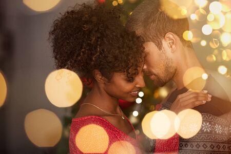 Pareja romántica en suéteres bailando antes de la víspera de año nuevo en casa. Joven encantador y mujer africana abrazándose sobre luces de Navidad bokeh. Pareja multiétnica bailando enamorado con luces doradas bokeh de fondo.