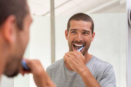 Lächelnder junger Mann mit Zahnbürste, der Zähne putzt und Spiegel im Badezimmer schaut. Hübscher junger Mann, der sich morgens im Badezimmer die Zähne putzt. Glücklicher Kerl im Pyjama, der nachts vor dem Schlafengehen die Zähne putzt. Standard-Bild