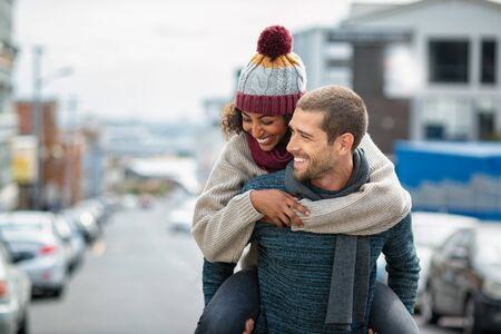 Smiling man giving piggyback ride to woman in the city. Young multiethnic couple in cold clothes walking in street and having fun. Cheerful girlfriend with wool cap and boyfriend in sweater enjoying w