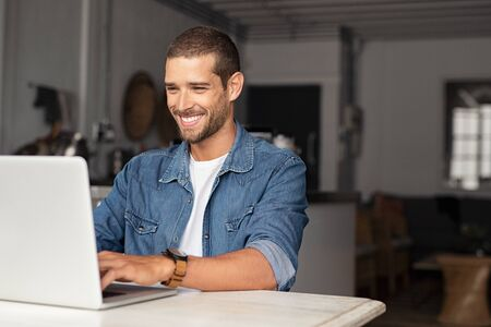 Happy young businessman using laptop at home. Young man working on computer at home. Casual entrepreneur feeling excited about new project while working on laptop at home. 写真素材