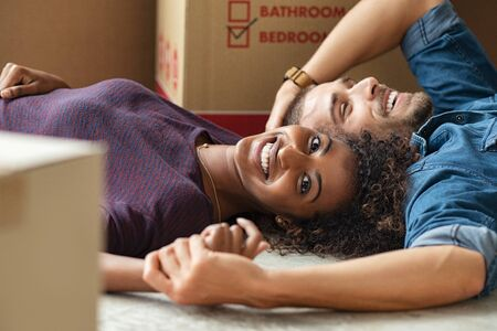 Happy multiethnic couple smiling while lying on floor near cardboard boxes. Portrait of african woman looking at camera while cheerful man lying on the floor of their new home. Young casual couple mov
