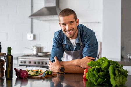 Handsome young man leaning on kitchen counter with vegetables and looking at camera. Smiling man wearing apron while preparing food at home. Portrait of happy casual guy leaning on steel counter in th