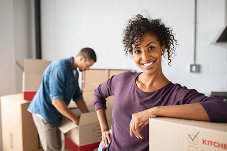 Portrait of beautiful smiling woman leaning on cardboard boxes at new apartment. Young multiethnic couple moving to a new home. Happy satisfied african girl looking at camera while her boyfriend unpac 写真素材