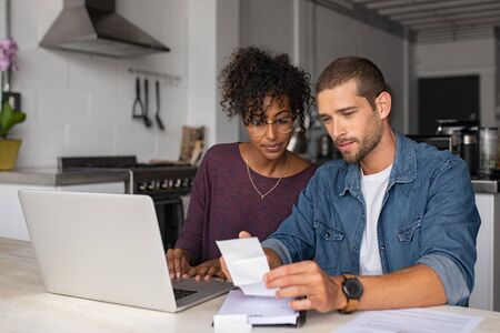 Young multiethnic couple checking bills while managing accounts on home banking app. Serious guy and african woman sitting at home discussing finance for the month. Young casual man and girl using lap