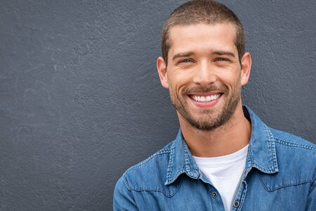 Closeup portrait of a happy young man smiling on gray background. Handsome casual guy with beard looking at camera. Portrait of a cheerful stylish man isolated against gray wall with copy space. 写真素材