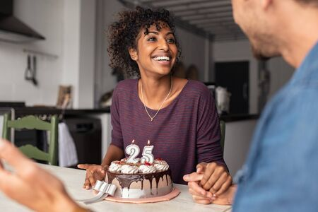 Multiethnic couple sitting at table and celebrating birthday at home in living room. Young african girl surprised on seeing 25th birthday cake with her boyfriend. Excited wife celebrating birthday wit