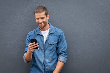 Young man leaning against a grey wall using mobile phone with copy space. Happy casual guy messaging on smartphone on gray background. Cheerful man looking down while typing and reading a message on c 写真素材