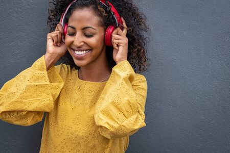 African girl listening to music with her wireless headphones while leaning against grey wall. Beautiful young woman listening music with closed eyes. Happy black woman wearing headphones enjoying the  写真素材