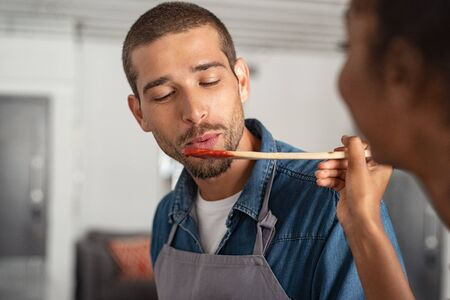 Closeup face of young man blowing on spoon to taste tomato sauce while woman cooking in kitchen. Guy in apron tasting food for dinner. Girl offering to her boyfriend a wooden spoon with sauce to taste 写真素材