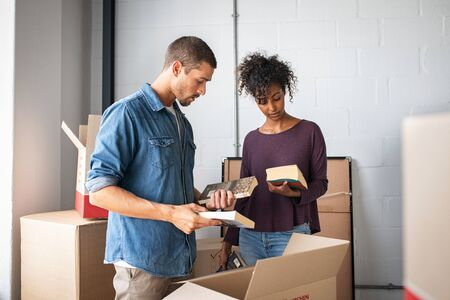 Multiethnic couple reading books while unpacking stuff after relocating to a new flat. Young man and african woman packing cardboard boxes with books. Guy and girl moving house. 写真素材