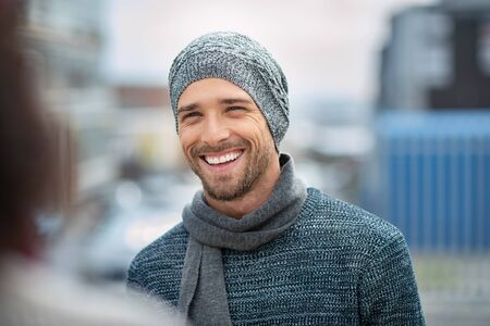 Young man wearing winter hat and scarf laughing while talking to woman. Handsome guy standing on a sidewalk wearing jumper and cashmere scarf. Portrait of cheerful man in winter clothes enjoying outdo