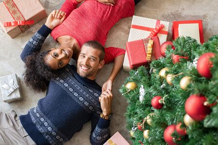 Young man and african woman lying on floor near christmas tree with presents. Top view of happy multiethnic couple lying down on floor near xmas gifts holding hands and looking at camera. High angle v