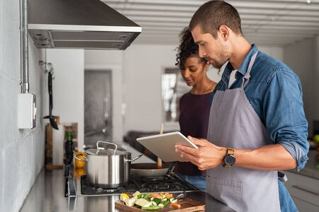 Man and beautiful woman preparing lunch while looking recipe from digital tablet. Young multiethnic couple using computer while cooking in kitchen at home. Husband and wife cooking pasta together acco