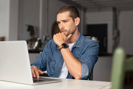 Serious young man working on laptop at home. Focused entrepreneur working on computer sitting at table. Thoughtful worried guy reading important articles and working on computer. 写真素材