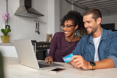 Smiling young couple making shopping online with credit card and laptop at home. Happy multiethnic couple holding debit card while buying on ecommerce site using laptop. Cheerful guy and african girl  写真素材