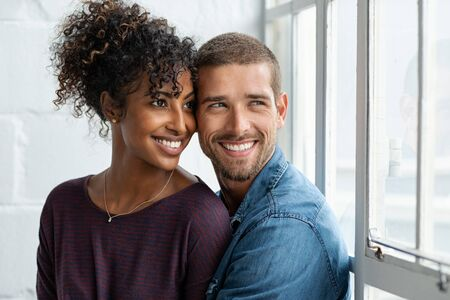 Loving multiethnic couple embracing and sitting near window. Happy girlfriend and smiling boyfriend looking away and thinking about their future together. Young man and african woman contemplating. 写真素材