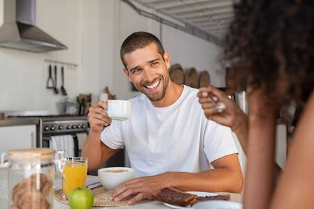 Young  smiling man and african woman having breakfast together with cup of coffee at home. Laughing multiethnic couple in conversation while eating milk and cereals . Smiling guy drinking cappuccino w